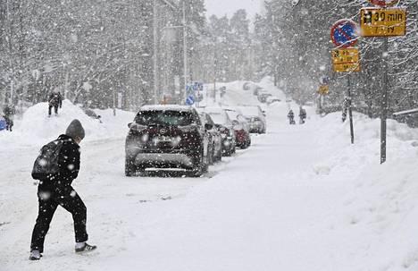Jalankulkija lumisateessa Etelä-Haagassa Helsingissä 19. tammikuuta.