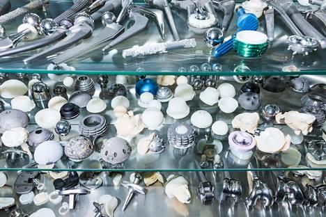 Ortonin sairaalan vitriinissä on valikoima tekonivelten osia, jotka ovat olleet jo kovassa käytössä.