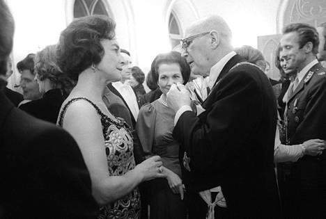 Raija Orasen romaanin pääpari Anita Hallama ja Urho Kekkonen seurustelevat Presidentinlinnan kutsuilla itsenäisyyspäivänä vuonna 1975.