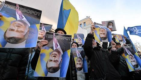 Mielenosoittajat pitivät Ukrainan presidentin Viktor Janukovytshin kuvaa ylösalaisin Kiovassa sunnuntaina.