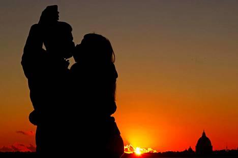 Pariskunta suuteli ja otti selfietä vuoden viimeisen auringonlaskun edessä Roomassa Italiassa.