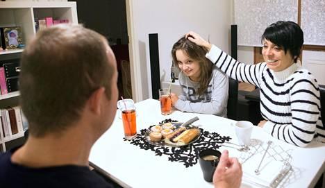 Kreikkalaisperhe Thanos Liveris (vas.), Liliana Liveri ja Maria Nikolakopoulou nautti herkkuja ruokapöydässä.