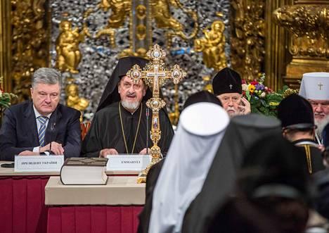Ukrainan presidentti Petro Porošenko (vas.), ekumeenisen patriarkaatin metropoliitta Emmanuel ja patriarkka Filaret kirkolliskokouksessa Kiovan Pyhän Sofian katedraalissa lauantaina.