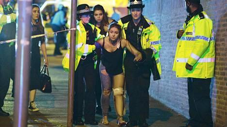 Poliisit auttoivat haavoittunutta konserttikävijää itsemurhapommittajan iskettyä Manchesterissa myöhään maanantai-iltana. Sadat lapset, nuoret ja aikuiset pakenivat Manchester Arena -konserttihallista, kun sen tiloissa räjähti.