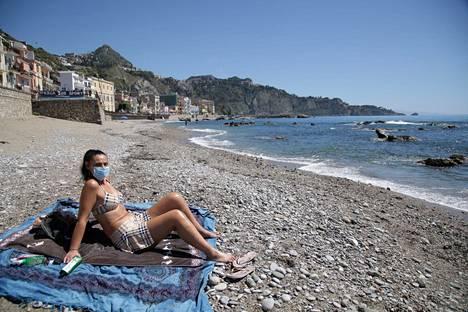 Nainen otti aurinkoa kasvomaskin kanssa Naxoksen rannalla Italian Taorminassa keskiviikkona.