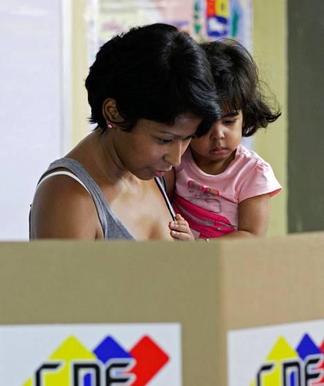 Äiti äänesti lapsensa kanssa Caracasissa sunnuntaina.