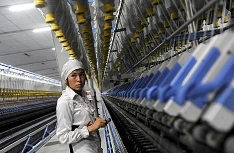 Kiinalaisnainen työssään tekstiilitehtaassa Aksun kaupungissa Xinjiangin uiguurien autonomisella alueella heinäkuun lopulla.