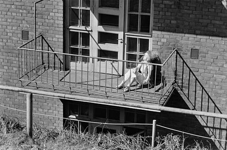 Nainen ottaa aurinkoa tuuletusparvekkeella Helsinginkadulla vuonna 1970.
