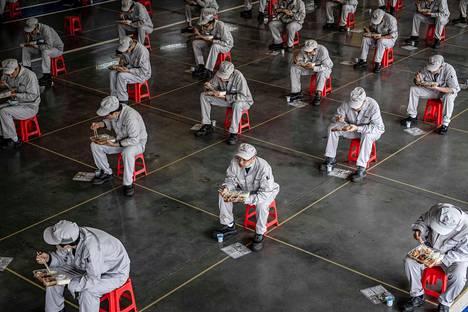 Autotehtaan työntekijöitä lounastauolla Wuhanin kaupungissa Kiinassa, jossa koronavirus havaittiin ensimmäisenä. Nyt ihmiset ovat saaneet jo palata töihin ja julkinen liikenne toimii taas.
