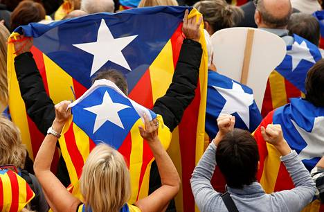 Ihmiset kannattelivat itsenäisyysmielisten tähtilippuja mielenosoituksessa Katalonian johtajiin kohdistettuja oikeudenkäyntejä vastaan Barcelonassa marraskuussa.