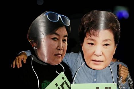 Mielenosoittajat olivat torstaina pukeutuneet naamareihin, joissa esiintyivät Etelä-Korean presidentti Park Geun-hye (oik.) ja tämän epävirallinen neuvonantaja Choi Soon-sil.