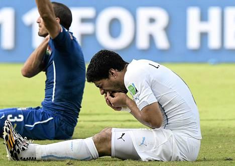 Uruguayn Luis Suárez tunnusteli hampaintaan puraisun jälkeen tiistain ottelussa. Taustalla purennan kohde, Italian Giorgio Chiellini.