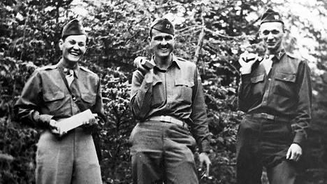 Amerikkalaisupseereita poseeraamassa kultaharkkojen kanssa niiden virallisella löytöpaikalla Walchensee-järvestä kohoavalla rinteellä. Henkilöt vasemmalta oikealle: majuri William Geiler, kapteeni George Garwood ja kapteeni Walter R. Dee. Kirjan kuvitusta.