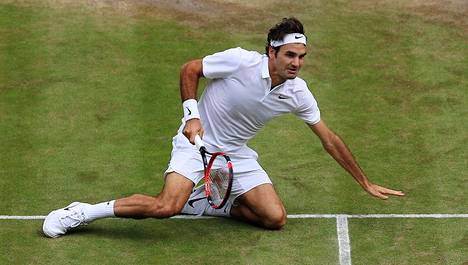 Sveitsin Roger Federer makasi kentän pinnassa Wimbledonin tennisturnauksessa vuonna 2016 ottelussaan Milos Raonicia vastaan.