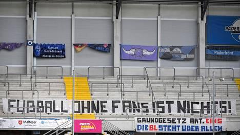 """""""Jalkapallo ilman faneja ei ole mitään"""", luki SC Paderbornin ja Borussia Mönchengladbachin välisen Saksan Bundesliiga-ottelun katsomossa 20. kesäkuuta. Bundesliiga aloitti suurista jalkapallosarjoista ensimmäisenä pelit kahden kuukauden koronatauon jäljiltä toukokuussa."""