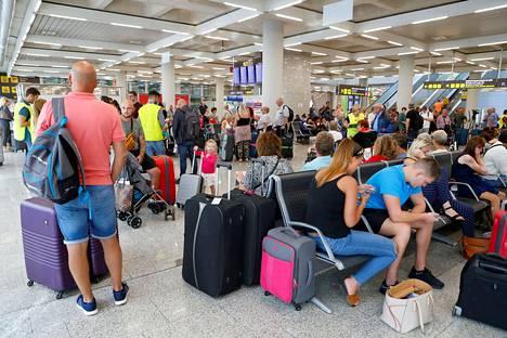 Epätietoisia lomamatkalaisia Mallorcan lentoaseman Thomas Cookin lähtöselvitysalueella maanantaina.