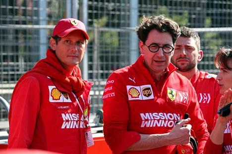 Ferrarin kilpailukykyongelmat myöntävä puheenjohtaja John Elkann (vas.) vakuuttaa luottavansa vierellään seisovaan tallipäällikkö Mattia Binottoon. Kuvassa kaksikko Azerbaidžanin gp:ssä 2019.