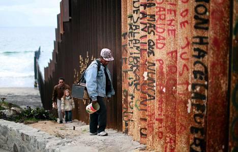 Mies käveli Yhdysvaltain ja Meksikon välisen raja-aidan vierellä Tijuanassa Meksikossa sunnuntaina. Yhdysvalloissa on viime aikoina kiistelty presidentti Barack Obaman ajamista maahanmuuttopolitiikan uudistuksista.