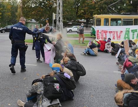 Poliisi suihkutti kadulle asettuneita Elokapinan mielenosoittajia Unioninkadun ja Kaisaniemenkadun risteyksessä lauantaina.