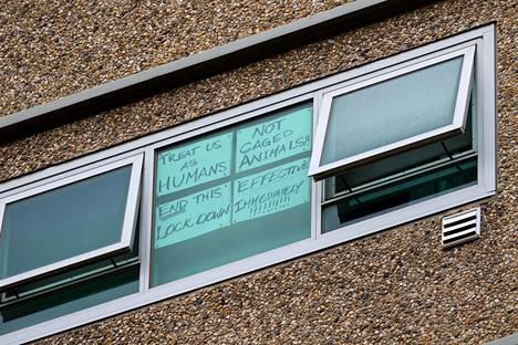 """""""Kohdelkaa meitä ihmisinä, ei häkissä olevina eläiminä"""", lukee ikkunaan kiinnitetyssä paperissa yhdessä eristetyistä kerrostaloista."""