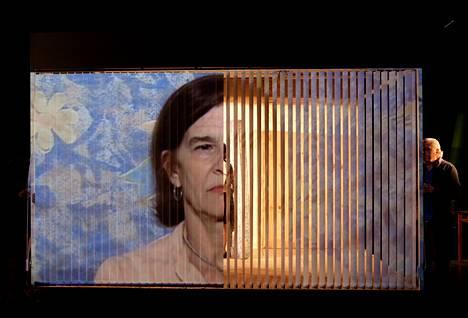 Elvira Onetto (näyttämölle heijastetussa videokuvassa) näyttelee äitiä esityksessä, joka käsittelee muun muassa mielenosoituksia mahdollisena lääkkeenä mielen sairauksiin.