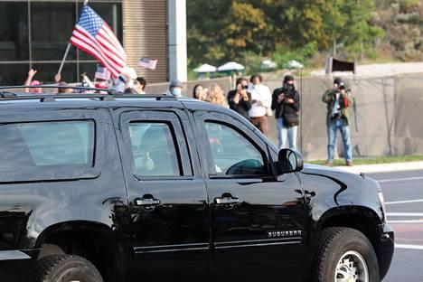 Erikoisvarustellun SUV-katumaasturin takapenkillä istunut Trump nosti peukut pystyyn kannattajilleen.