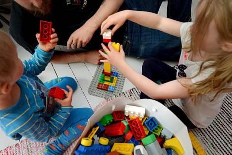 Isä leikkii lastensa kanssa duploilla Helsingissä kesällä 2015.