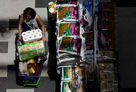 Singaporelainen nainen varustautui pahenevaan koronavirustilanteeseen supermarketissa perjantaina.