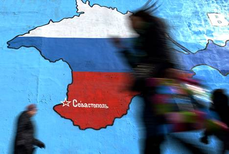 Ohikulkijoita kävelee seinään maalatun Krimin niemimaan kartan ohi Moskovassa 31. maaliskuuta. Krim on maalattu Venäjän lipun värein.