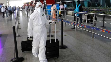 Suojapukuun pukeutunut matkustaja veti lentolaukkua Indira Gandhin lentokentällä New Delhissä maanantaina.