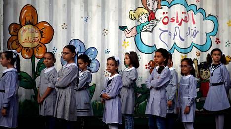 Palestiinalaislapset seisovat jonossa UNRWA:n koulun pihalla.