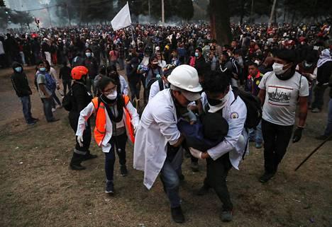 Pelastushenkilökunta auttoi protesteissa loukkaantunutta henkilöä perjantaina 11. lokakuuta Quitossa.