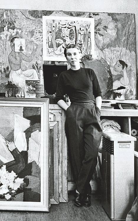 Tove Jansson ateljeessaan vuonna 1956. Ylhäällä taustalla freskon luonnos, jonka päällä on Sam Vannin grafiikanvedos. Lattialla Janssonin maalauksia. Kirjan kuvitusta.