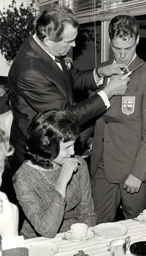 Lontoon kultamitalimies Tapio Rautavaara oli varannut naskalin mukaansa, saadakseen Nevalan takin rintaan reiän ja kiinnittääkseen siihen Kultamitalimiehet r.y:n merkin. Edessä Nevalan morsian Mirja Peltonen.