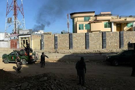Afganistanin turvallisuuspalvelun työntekijät partioivat savuavan presidentinlinnan lähellä Kabulissa tiistaina.