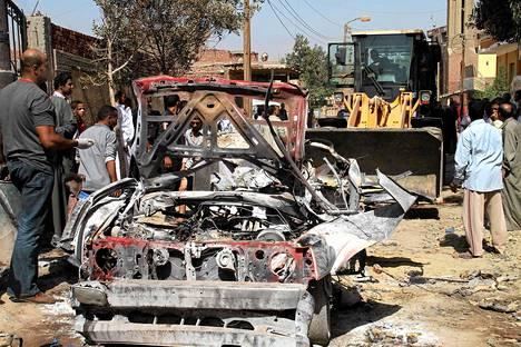 Paikalliset tutkivat ennenaikaisesti räjähtäneen pommin tuhoamaa autoa Shurafassa Etelä-Kairossa 30. heinäkuuta.