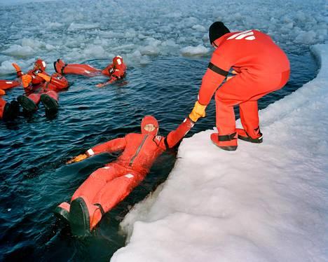 Turisteja kellumassa kuivapuvuissa jäämurtaja Sampolla tehdyllä retkellä viime vuoden maaliskuussa.