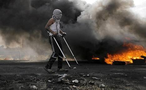 Palestiinalainen mielenosoittaja käveli kainalosauvojen avustamana lähellä juutalaisten siirtoasutusta Bet Elissä Ramallahissa.