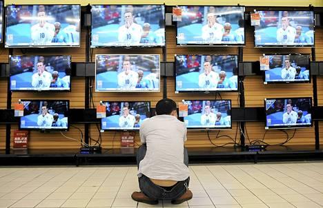 Mies seurasi tv-lähestystä kodinkoneliikkeessä Wuhanin kaupungissa keskisessä Kiinassa kesäkuussa.