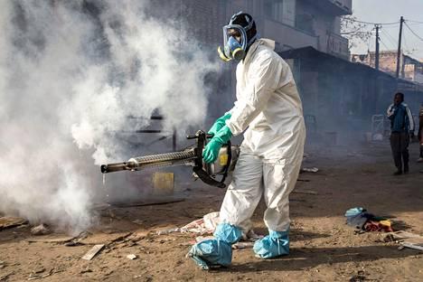 Työntekijä puhdistamassa katuja Dakarissa Senegalissa. Maan hallitus on yrittänyt torjua viruksen leviämistä kovilla toimilla.