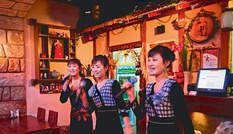 """Pohjoiskorealaiset tarjoilijat """"Tanja"""", """"Aljona"""" ja """"Lina"""" esittävät kotimaansa isänmaallisia lauluja asiakkaille pohjoiskorealaisessa ravintolassa Vladivostokissa."""