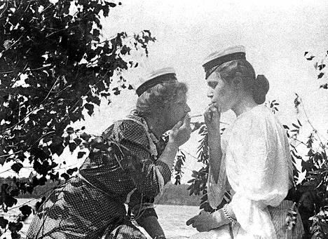 """Tyyni Hjelt ja Anna Becker yrittävät opetella """"paheita"""", lukee 1900-luvun alussa otetun kuvan takana."""
