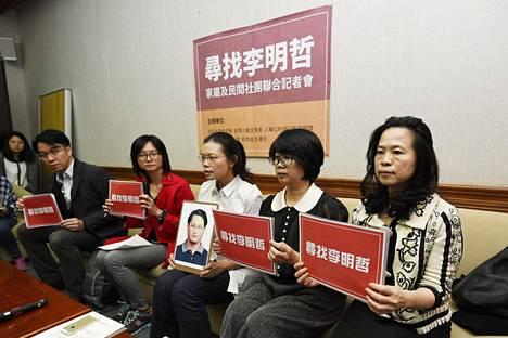 """Lee Ming-chehin puoliso Lee Ching-yu esitteli kadonneen miehensä kuvaa lehdistötilaisuudessa Taipeissa viime viikolla. Lee Ching-yu'n vieressä istuvat järjestöjen edustjaat pitelevät kylttejä, joissa lukee """"löydämme Lee Ming-chehin""""."""