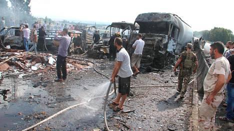 Syyrian asevoimien sotilaat ja siviilit tutkivat tuhoja Tartousin kaupunkiin johtavan sillan lähellä pommi-iskun jälkeen.