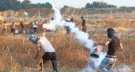 Mielenosoittaja heitti takaisin Israelin joukkojen kyynelkaasukranaatin torstaina lähellä Israelin ja Gazan rajaa.