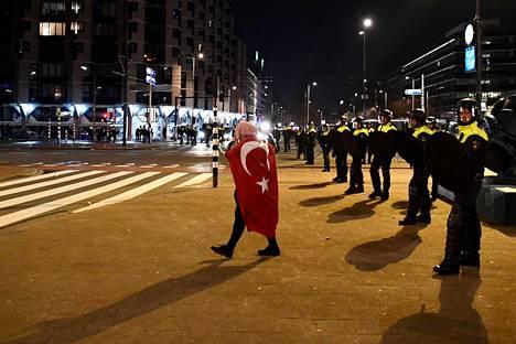 Turkin lippuun kääriytynyt mies käveli mellakkapoliisin edessä Turkin konsulaatin lähistöllä Rotterdamissa sunnuntaina.