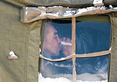 Asunnoton mies joi torstaina teetä väliaikaissuojassa ukrainalaisessa Donetskin kaupungissa.
