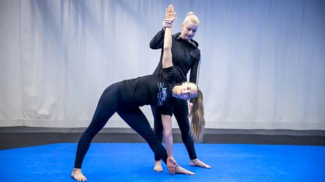 Roosa Närhi avustaa Titta Keinästä kiertämään vartaloa kolmioasennossa.