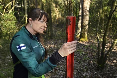 Tawastia Trail Clubin puheenjohtaja Kaija Järvi ja kylmästä sodasta muistuttava tolppa metsikössä Hämeenlinnassa.