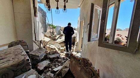 Mies käveli tuhoutuneessa rakennuksessa Tripolin Znatahin kaupunginosassa vapunpäivänä. Taistelut Libyan pääkaupungin ympärillä ovat jatkuneet ja sotapäällikkö Khalifa Haftarin joukot ovat pommittaneet esikaupunkeja.